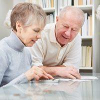 Senioren Paar rechnet mit Taschenrechner
