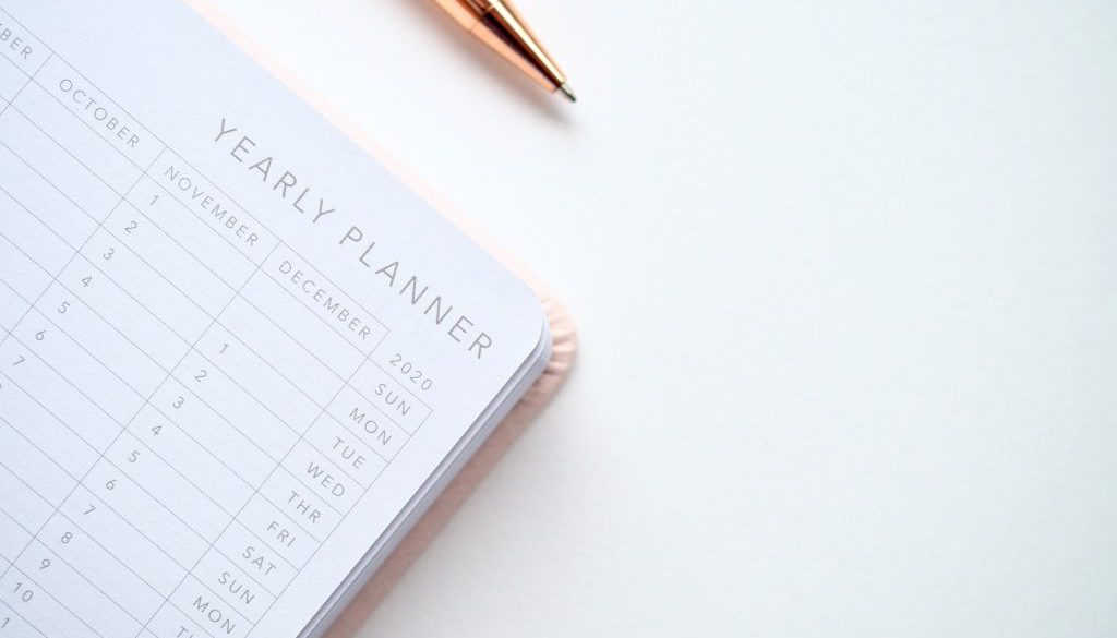 close-up-photo-of-yearly-planner-beside-a-pen-1558691