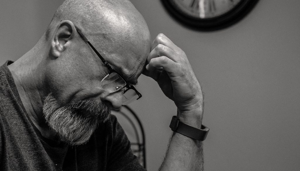 grayscale-photo-of-man-thinking-in-front-of-analog-wall-1194196
